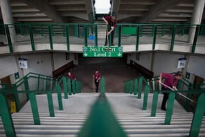 Wimbledon photo book: The workforce cleans an entrance and signs around Court 1