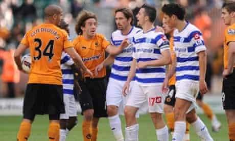 QPR's Joey Barton is held back by Stephen Hunt of Wolves after a clash with Karl Henry