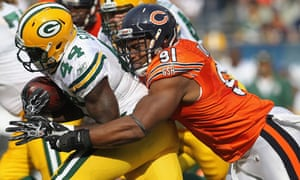 Amobi Okoye #91 of the Chicago Bears brings down James Starks #44 of the Green Bay Packers