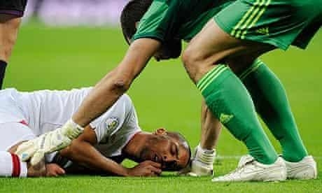 England's Theo Walcott lies injured at Wembley