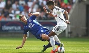 Everton's Phil Jagielka, left, contests the ball with Swansea City's Scott Sinclair.