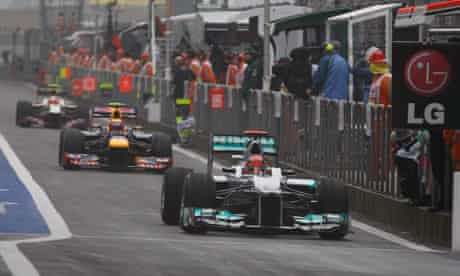 Michael Schumacher leads Red Bull's Mark Webber out of the pit lane