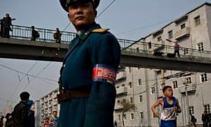 Runners pass under a pedestrian bridge in central Pyongyang during the marathon