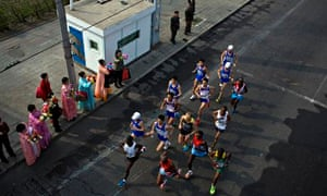 The leading pack of runners in the Pyongyang Marathon are cheered on by North Korean spectators