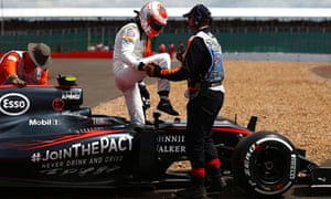 Jenson Button climbs out of his car after retiring on the first lap of the British Grand Prix