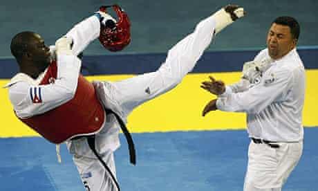 Angel Valodia Matos of Cuba kicks out at referee Chakir Chelbat of Sweden