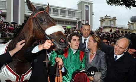 Jockey Christophe Soumillon with Zarkava poses with owner Aga Khan after winning the Qatar Prix de l'Arc de Triomphe