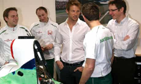 Britain's Jenson Button talks to mechanics and other team members at the Honda F1 plant in Brackley