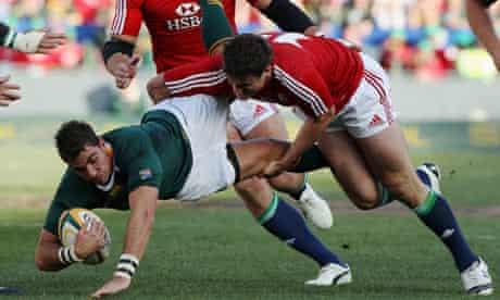Ruan Pienaar is thrown to the ground by Jamie Roberts
