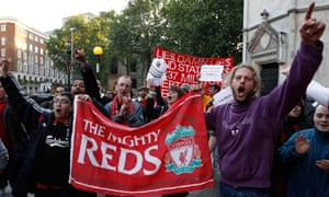 Liverpool Football Club supporters hold banners outside the High Court in London