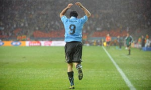 Uruguay's Luis Suárez celebrates after scoring his second during a rain-lashed 2-1 victory