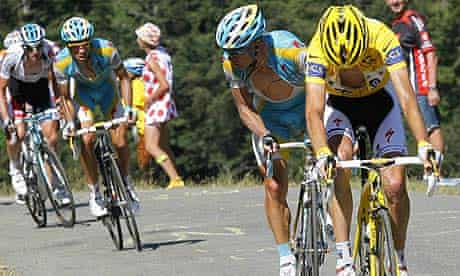Andy Schleck (right) looks at his chain as he rides with Alberto Contador