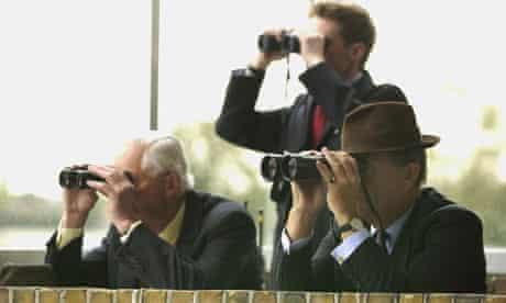 Horse racing stewards watch through binoculars
