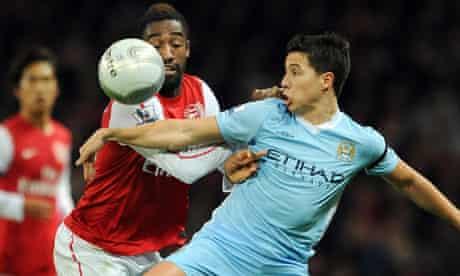 Arsenal's Johan Djourou, left, and Manchester City's Samir Nasri battle for the ball