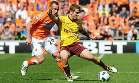Jack Wilshere controls the ball under pressure from Charlie Adam during Arsenal's win over Blackpool