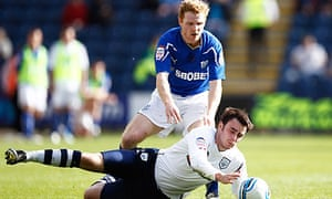 Preston's Keith Treacy falls under a challenge from Chris Burke during his side's loss to Cardiff