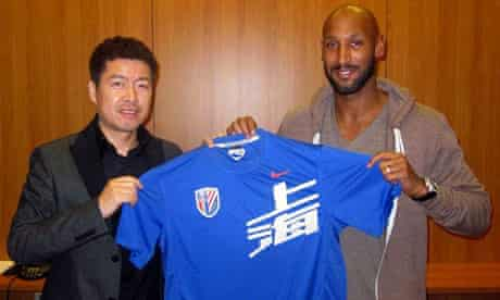 Nicolas Anelka holds a jersey of Shanghai Shenhua club