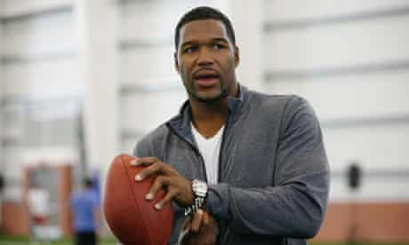 Michael Strahan posing with a ball
