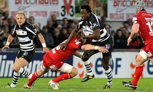 Brive's wing Jacques Boussuge is tackled by Scarlet's No8 Ben Morgan