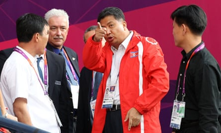 North Korean official Son Kwang-ho talks to other officials after the team walked off at Hampden