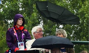 Spectators shelter from rain during the London 2012 Olympics tennis