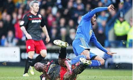 Matthew Barnes Homer of Macclesfield Town is tackled by Adedeji Oshilaja of Cardiff City