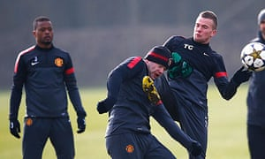 Patrice Evra looks on as Tom Cleverley, right, and Wayne Rooney clash