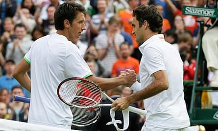 Sergiy Stakhovsky, left, shakes hands with Roger Federer after he defeated him in their men's second