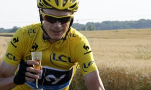 Chris Froome rides with a glass of champagne