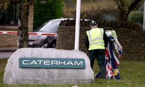 A security guard removes the flags from the Caterham factory in Leafield, Oxfordshire
