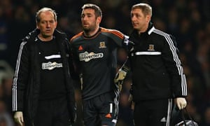 Hull's injured goalkeeper Allan McGregor is escorted from the field after being sent off.