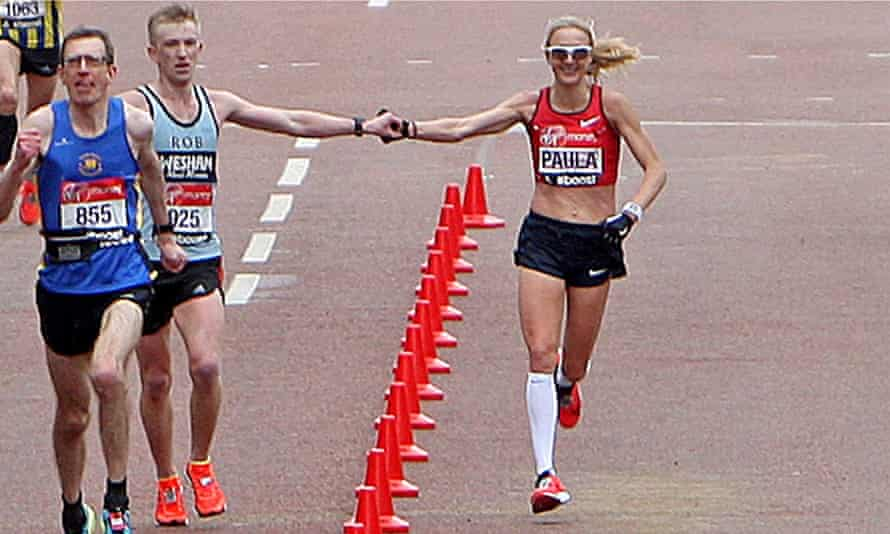 Paula Radcliffe joins hands with a fellow runner as she reaches the finish of the London Marathon.
