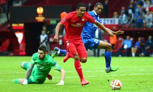 Sevilla's Carlos Bacca rounds Dnipro goalkeeper Denys Boyko on the way to scoring the Spanish side's