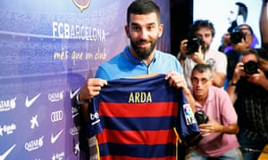 Arda Turan poses with a Barcelona shirt soon after signing for the club in July