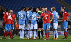 Lazio and Napoli players surround referee Massimiliano Irrati as he halts their match in Rome