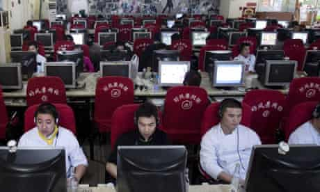 People use computers at an internet cafe in Beijing