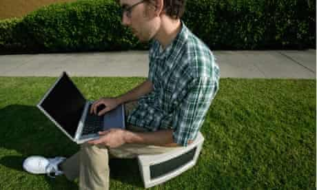 Young man sitting on computer monitor in grass
