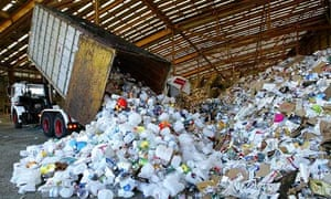 A truck dumps its load of plastic at a waste recycling facility
