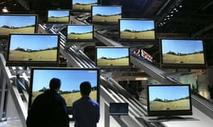 Two attendees look at a display of flat screen televisions at the Consumer Electronics Show