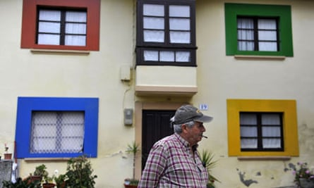 A man stands in front of a decorated house in the small village of Sietes, northern Spain