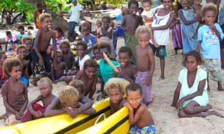 island kids gather round the family's kayaks