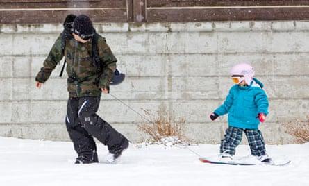Parent teaching child on snowboard