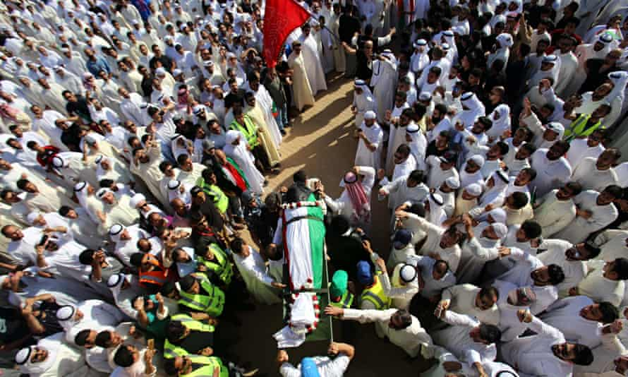 Mourners carry the body of one of the vi