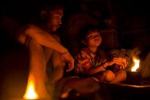 Mattias Klum gallery: Camp of nomadic Penan at night in Borneo's rainforest