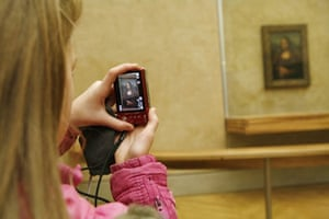 Earthbound images: Tourists photographing the Monna Lisa, Musee Louve, Paris