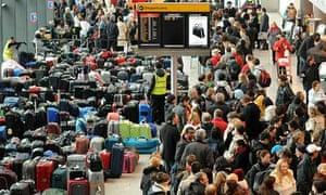 Airline passengers (R) queue beside rows