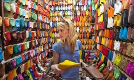 A western woman tourist buying shoes at Marrakesh souk, shoe shop, Morocco.