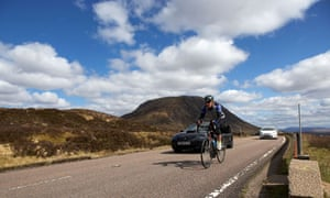 Cyclist on the A82 road in Glen Coe in the Scottish Highlands