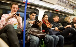 Tube through the decades: Passengers using mobile technology on a london underground train