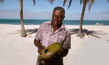 North Beach owner Reuben James prepares a coconut